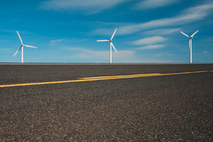 Three wind turbines on the horizon and a road running through the plains near the Columbia River Gorの写真素材 [FYI02258103]