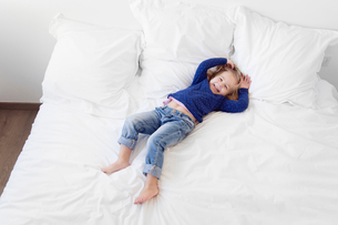 High angle view of girl with blond hair wearing jeans and blue top lying on her back on a bed.の写真素材 [FYI02258115]