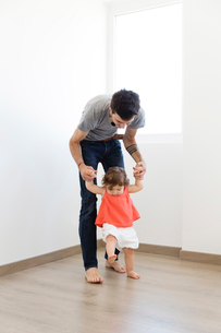 Man wearing grey T-shirt and jeans standing behind baby girl in red dress, holding her hands, walkinの写真素材 [FYI02258123]