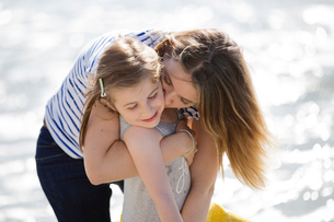 Blond woman wearing stripy T-shirt standing on beach, hugging girl.の写真素材 [FYI02258126]