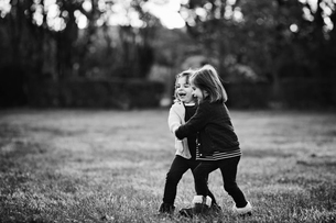 Two young girls, twin sisters, holding hands, playing on a lawn.の写真素材 [FYI02258134]