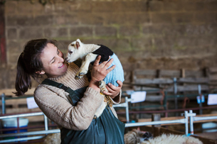 Woman standing in a barn, holding a newborn lamb dressed in a knitted jumper.の写真素材 [FYI02258145]