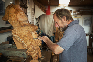 A craftsman, a wood carver working on a wooden female ship's figurehead held in a vice on the workbeの写真素材 [FYI02258164]