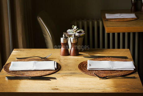Wooden table set with place mats, napkins and cutlery in a restaurant.の写真素材 [FYI02258169]
