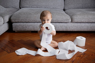Baby boy with blond hair sitting on hardwood floor, playing with toilet paper rolls.の写真素材 [FYI02258171]