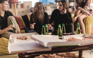 Three young women and young man sitting on a sofa, smiling, pizza and beer bottles on coffee table.の写真素材 [FYI02258173]