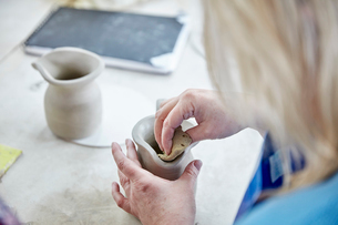 A woman using her hands to shape and smooth a wet clay jug to match another, making a pair.の写真素材 [FYI02258181]