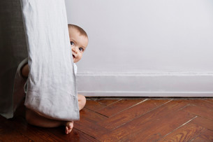 Baby boy with blond hair sitting on hardwood floor, peering from behind curtain.の写真素材 [FYI02258183]