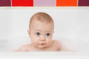 Baby boy sitting in a bathtub, having foam bath.の写真素材 [FYI02258184]