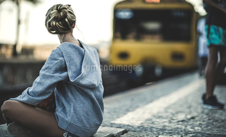 Young woman sitting on a railway station platform with a train behind.の写真素材 [FYI02258192]