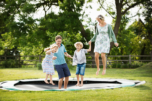 Man, woman, boy and girl holding hands, jumping on a trampoline set into the ground in a garden.の写真素材 [FYI02258196]