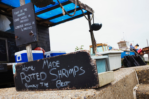 Handwritten sign advertising home made potted shrimp outside a fish shop in a Suffolk harbour.の写真素材 [FYI02258225]