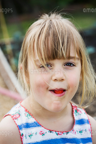 Smiling girl eating a strawberry, looking at camera.の写真素材 [FYI02258232]