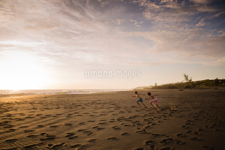 Two children running across the sand towards the sea, at sunset.の写真素材 [FYI02258236]