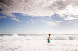 Young boy playing at the water's edge on a sandy beach.の写真素材 [FYI02258239]