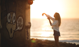 Young woman standing in front of a sunset throwing a basketball.の写真素材 [FYI02258240]