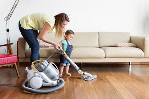 Woman and young boy wearing denim dungarees, standing in front of sofa, hoovering hardwood floor.の写真素材 [FYI02258267]