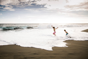 Two children, young boys playing at the water's edge on a sandy beach.の写真素材 [FYI02258269]