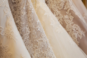 Rows of wedding dresses on display in a specialist wedding dress shop. Close up of full skirts, someの写真素材 [FYI02258280]