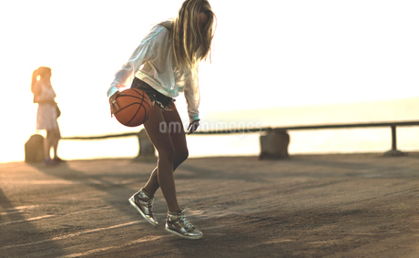 Young woman standing in front of a sunset bouncing a basketball.の写真素材 [FYI02258285]