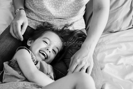 High angle view of woman sitting on a bed,  playing with smiling young girl.の写真素材 [FYI02258289]