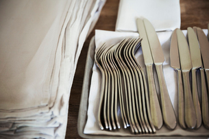 High angle close up of napkins and silver forks and knives on a table in a restaurant.の写真素材 [FYI02258302]