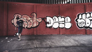 Young man playing with a ball in front of a wall of graffiti.の写真素材 [FYI02258304]