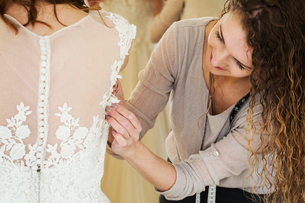 A young woman in a white wedding dress, and a dressmaker fitting the bodice and waist, adjusting theの写真素材 [FYI02258308]