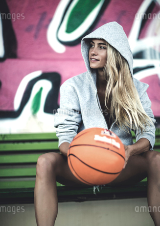 Young woman sitting on a bench holding a basketball.の写真素材 [FYI02258316]