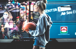 Young woman walking holding a basketball with a coach behind.の写真素材 [FYI02258319]