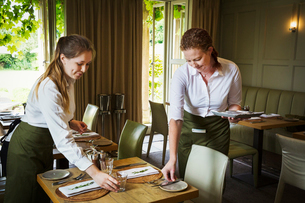Two women wearing aprons setting tables in a restaurant.の写真素材 [FYI02258320]