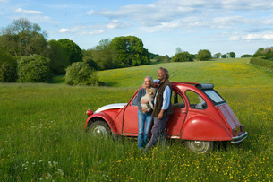 Man and woman standing side by side on a meadow, holding small dog, leaning against red vintage car.の写真素材 [FYI02258336]