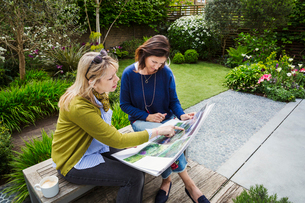 Two women sitting on a bench in a garden, looking at a portfolio with gardening images, discussing gの写真素材 [FYI02258351]