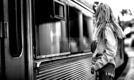 Young woman standing on a railway station platform next to a train.の写真素材 [FYI02258359]