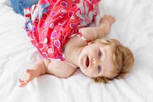 High angle view of young girl with ginger hair and blue eyes wearing a red dress, lying on bed.の写真素材 [FYI02258366]