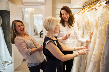Three women in a wedding dress boutique looking at a rail of white bridal gowns, with lace and decorの写真素材 [FYI02258380]