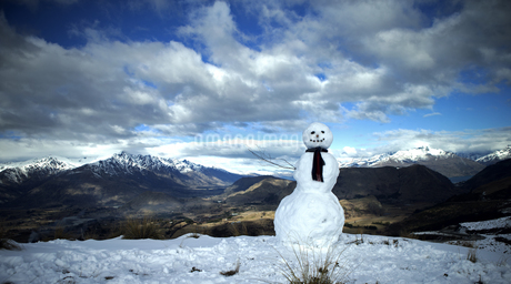 Snowman wearing a scarf, snow-capped mountains in the distance, cloudy sky.の写真素材 [FYI02258396]