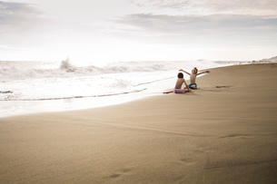 Two children, young boys playing at the water's edge on a sandy beach.の写真素材 [FYI02258399]