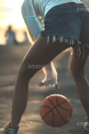 Rear view of a young woman standing in front of a sunset bouncing a basketball.の写真素材 [FYI02258406]