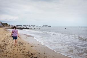 Rear view of woman walking barefoot along a sandy beach by the ocean.の写真素材 [FYI02258412]