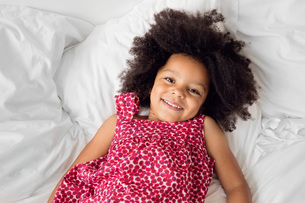 High angle view of girl with curly black hair lying on a bed, wearing printed top, smiling at cameraの写真素材 [FYI02258417]