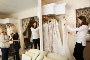 Three women, a client and two retail advisors in a wedding dress shop, looking through the choice ofの写真素材 [FYI02258449]