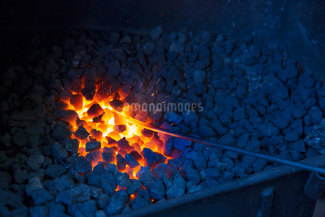 A glowing metal rod in the hot coals in a blacksmith's forge.の写真素材 [FYI02258451]