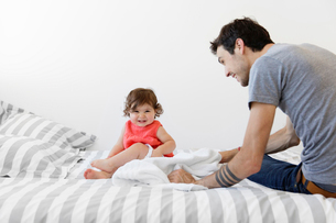 Man wearing grey T-shirt and jeans sitting on bed with stripy duvet, playing with baby girl in red tの写真素材 [FYI02258467]