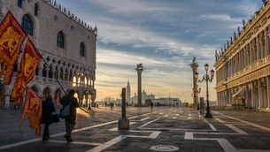 Two people carrying traditional flags walking across St Mark's Square, Venice, Italy, at sunrise.の写真素材 [FYI02258472]