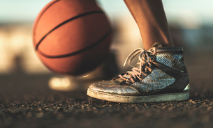 Close up of a basketball bouncing near a person's feet.の写真素材 [FYI02258478]