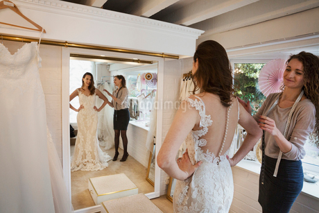 A young woman in a full length white wedding dress, looking at her reflection in the mirror in a briの写真素材 [FYI02258486]