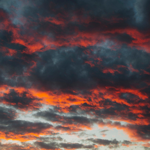 Black clouds in the sky, tinged orange and red by the setting sun.の写真素材 [FYI02258488]