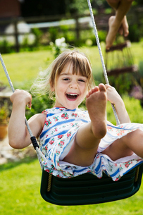 Smiling girl wearing a sundress on a swing in a garden.の写真素材 [FYI02258518]