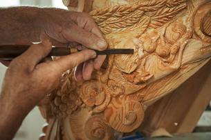 Close up of a craftsman at work, using a fine chisel to shape and chisel out the detail in decoratioの写真素材 [FYI02258527]